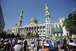 Image ©Licensed to i-Images Picture Agency. 28/07/2014. Xining. China. 61981797<br /> Muslims leave Dongguan Mosque after a prayer gathering in Xining, capital of northwest China's Qinghai Province, July 28, 2014. Muslims across the province gathered here on Monday to celebrate Eid Al-Fitr, marking the end of the Muslim fasting month of Ramadan. Picture by  imago / i-Images<br /> UK ONLY
