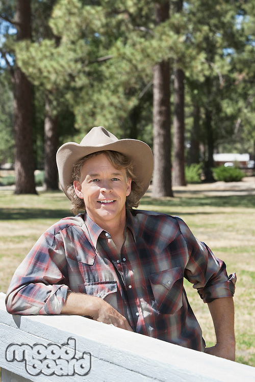 Mature man wearing cowboy hat leaning on wooden slab