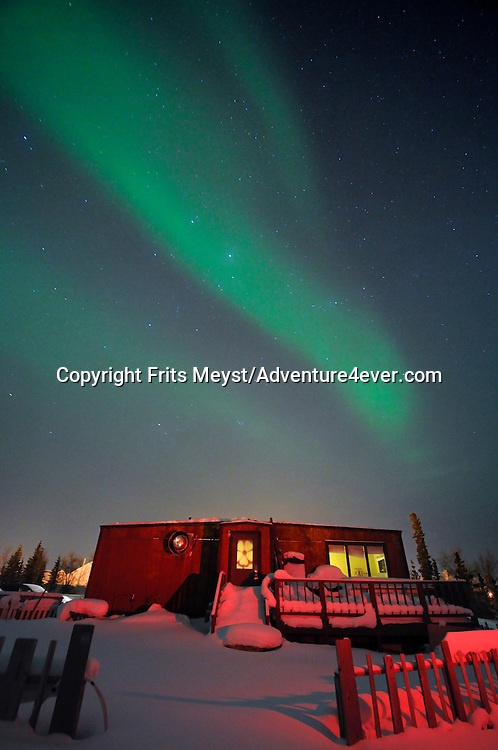 Gameti, Northwest Territories, Canada, February 2012. The Northern light over the motel and the ice road. The bright dancing lights of the aurora are actually collisions between electrically charged particles from the sun that enter the earth's atmosphere. The lights are seen above the magnetic poles of the northern and southern hemispheres. They are known as 'Aurora borealis' in the north and 'Aurora australis' in the south. Auroral displays appear in many colours although pale green and pink are the most common. Shades of red, yellow, green, blue, and violet have been reported. The lights appear in many forms from patches or scattered clouds of light to streamers, arcs, rippling curtains or shooting rays that light up the sky with an eerie glow. Photo by Frits Meyst/Adventure4ever.com