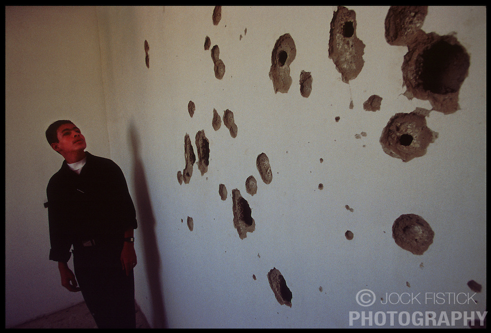 A Palestinian youth looks at a bullet riddled wall in an apartment building in the West-bank city of Bethlehem, which came under fire from Israeli soldiers. (Photo © Jock Fistick)