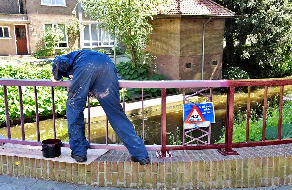 Nederland, Zutphen, 7-5-2018Een schilderd verft de metalen leuning van een bruggetje in de stad .Foto: Flip Franssen