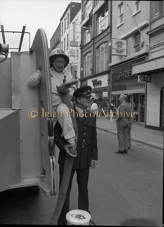 Maureen Potter with The Dublin Fire Brigade..1986..19.07.1986..07.19.1986..19th July 1986..Dublin Fire Brigade aided and abetted by Maureen Potter staged a collection,today,in aid of The Royal Victoria Eye and Ear Hospital,Adelaide Road,Dublin. It is hoped that the proceeds would go towards the purchase of a laser eye scanner. The Eye and Ear Hospital was established in 1897 and has served not only Dublin but the whole country as well...Image shows Maureen getting a supporting hand from a Dublin Fireman. Maureen with hose in hand is ready for action.