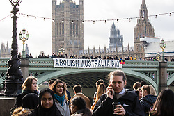 London, UK. 25th January, 2019. Activists drop a banner from Westminster Bridge, in view of the Houses of Parliament, to call for the abolition of Australia Day in advance of rallies in every Australian city on Australia Day tomorrow. The event was organised in solidarity with Aboriginal and Torres Strait Islander people who consider Australia Day, a day celebrating the colonisation of Australia, to be a day of mourning rather than a day of celebration. Aboriginal and Torres Strait Islander people will, instead, stage 'Invasion Day' and 'Survival Day' protests and commemorations across Australia.