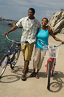 Couple walking with bicycles at beach