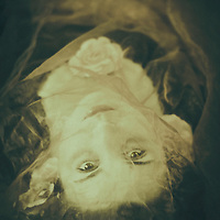 atmospheric and ghostly image of a young woman with open eyes lying under tulle material with roses in vintage style