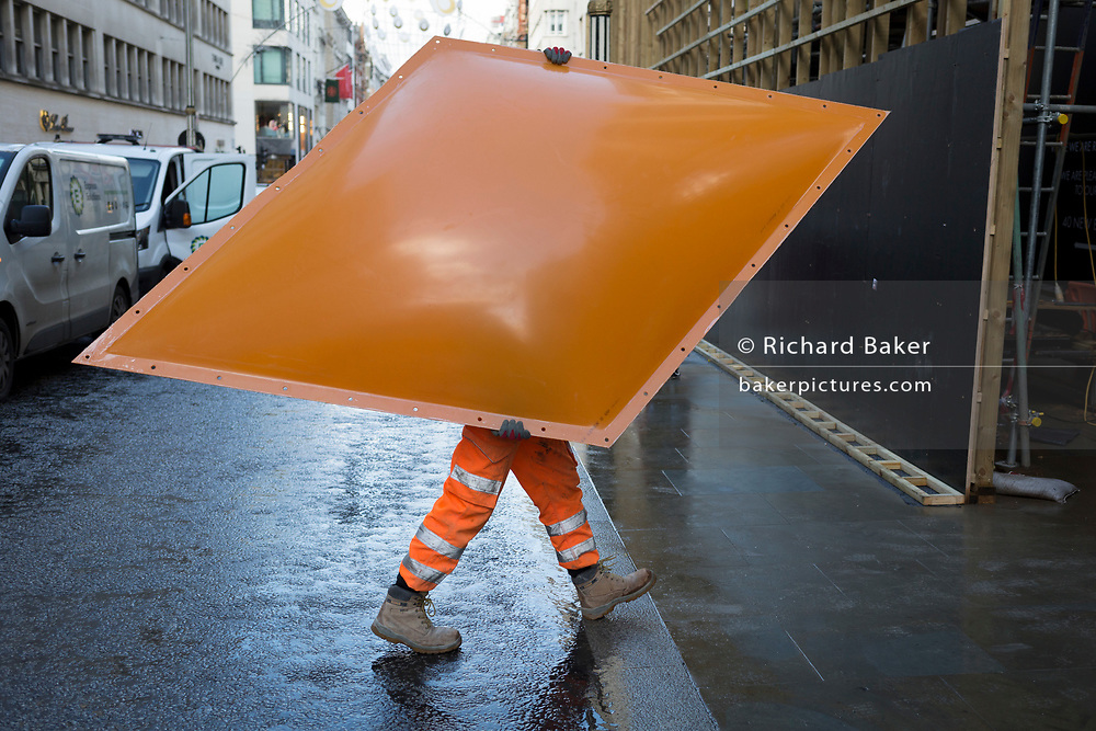 A workman carries a diamond-shaped item that will form part of the exterior facia to Louis Vuitton in Bond Street, during the shop's interior renovation, on 3rd December 2018, in London, UK
