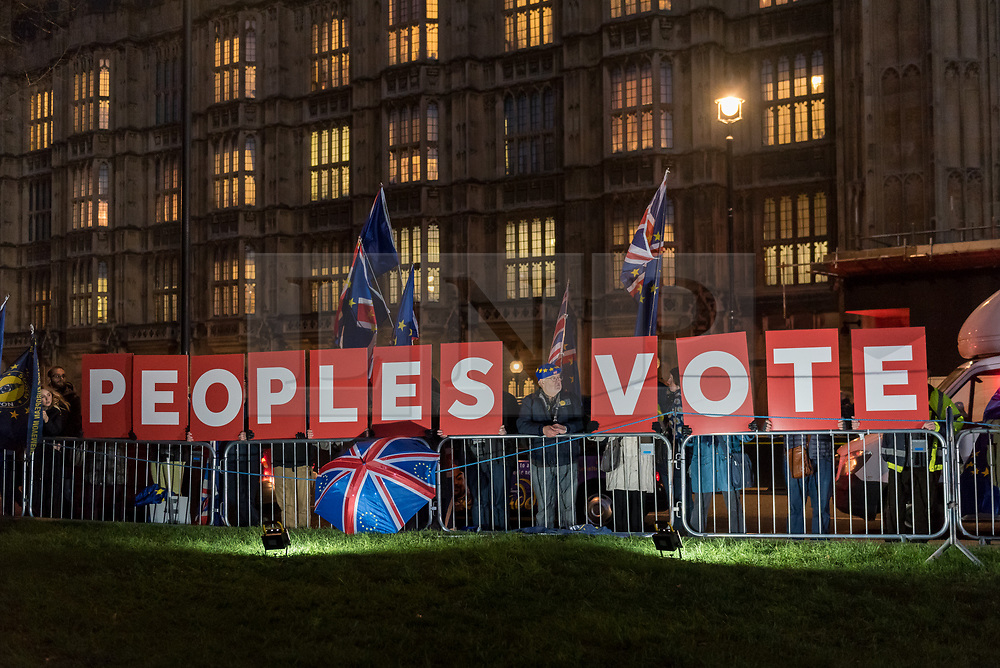 """© Licensed to London News Pictures. 11/12/2018. LONDON, UK. Signs showing the words """"Peoples Vote"""" are held up outside the House of Commons by anti-Brexit demonstrators from SODEM (Stand Of Defiance European Movement). Theresa May, Prime Minister, is touring European capitals to try to renegotiate the Brexit agreement with the European Union after today's meaningful vote by MP's was deferred.  Photo credit: Stephen Chung/LNP"""