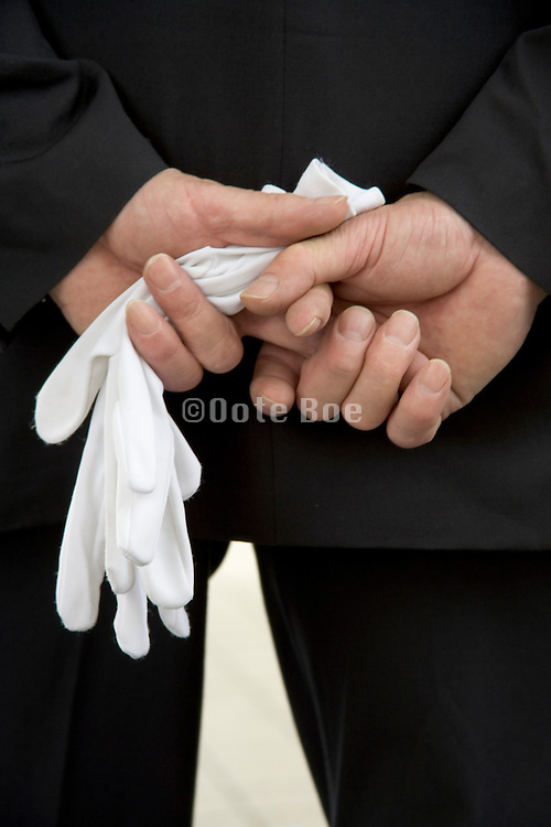 man standing and waiting with white gloves in his hand at a military memorial parade