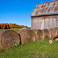 Six large round haybales stacked against a barn under a bright blue clear autumn sky.