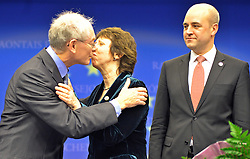 Herman Van Rompuy, Belgium's prime minister, and the first president of Europe, left, gives a kiss to Catherine Ashton, Europe's new foreign minister, center, as Fredrik Reinfeldt, Sweden's prime minister and standing president of the European Council, looks on, during the press conference following the European Union Summit at the EU headquarters in Brussels, Belgium, on Thursday, Nov. 19, 2009. European leaders set divisions aside today as they chose their first-ever European Union president to represent the 27-nation bloc on the world stage. (Photo © Jock Fistick)