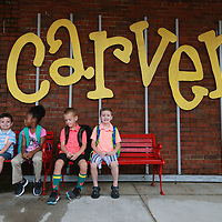 Cameron Kincaid, from left, Talia Griffin, Graves Daniel and Jase McRae wait in the bench before going inside Carver Elementary for their breakfast to start their first day of school.