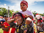 01 NOVEMBER 2015 - YANGON, MYANMAR: A man and his son at the NLD's last election rally of the 2015  election in the Yangon suburbs Sunday. Political parties are wrapping up their campaigns in Myanmar (Burma). National elections are scheduled for Sunday Nov. 8. The two principal parties are the National League for Democracy (NLD), the party of democracy icon and Nobel Peace Prize winner Aung San Suu Kyi, and the ruling Union Solidarity and Development Party (USDP), led by incumbent President Thein Sein. There are more than 30 parties campaigning for national and local offices.    PHOTO BY JACK KURTZ