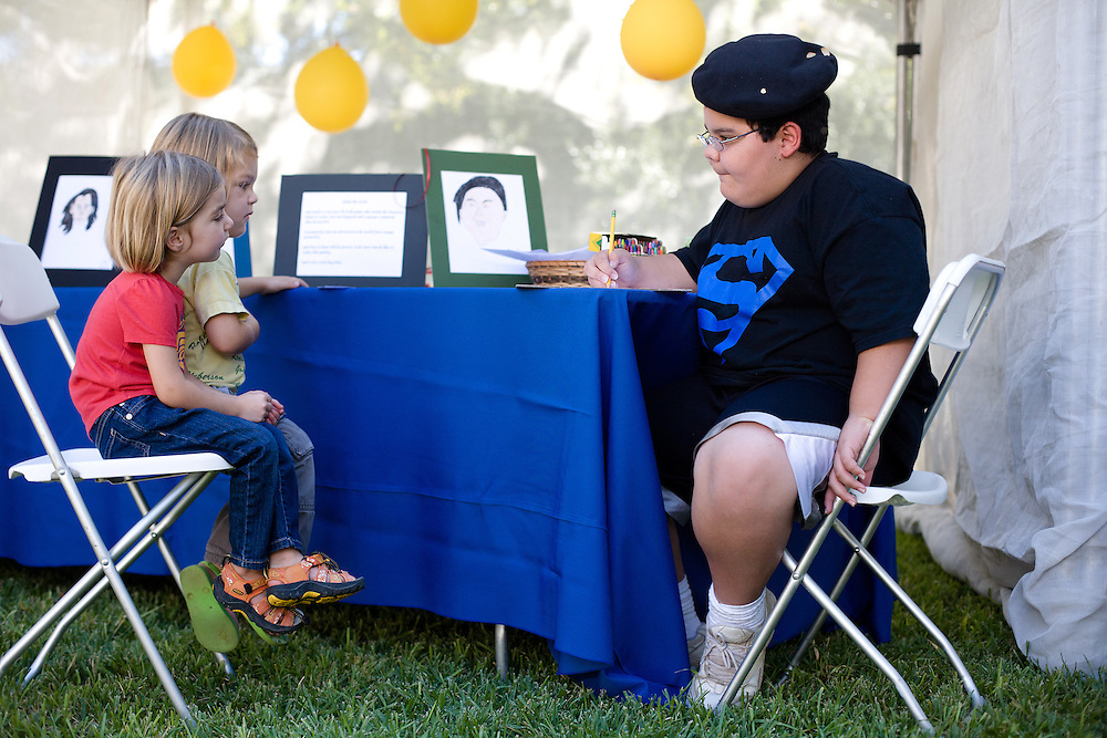 Samuel Battle, 10, right, makes a portrait of three-year-old twins, Scarlett and Luke Gromquist during the Children's Business Fair in Austin, Texas.