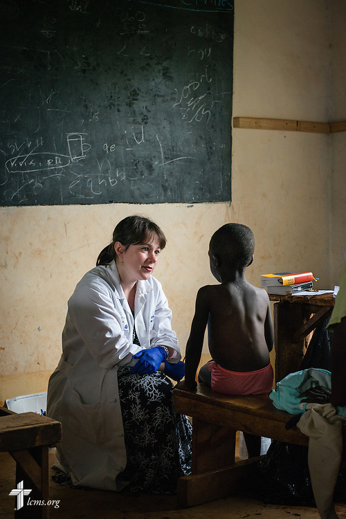 Dr. Katie Butler, a critical care surgeon from Boxford, Mass., attending Our Savior Lutheran Church in Topsfield, Mass., listens to a young boy as she and fellow members of the Mercy Medical Team treat patients from nearby villages Tuesday, June 10, 2014, at the Luanda Doho Primary School in Kakmega County, Kenya. LCMS Communications/Erik M. Lunsford