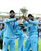 Moeen Ali of England and Adil Rashid of England hold the Cricket World Cup trophy on the lap of honour during the ICC Cricket World Cup 2019 Final match between New Zealand and England at Lord's Cricket Ground, St John's Wood, United Kingdom on 14 July 2019.