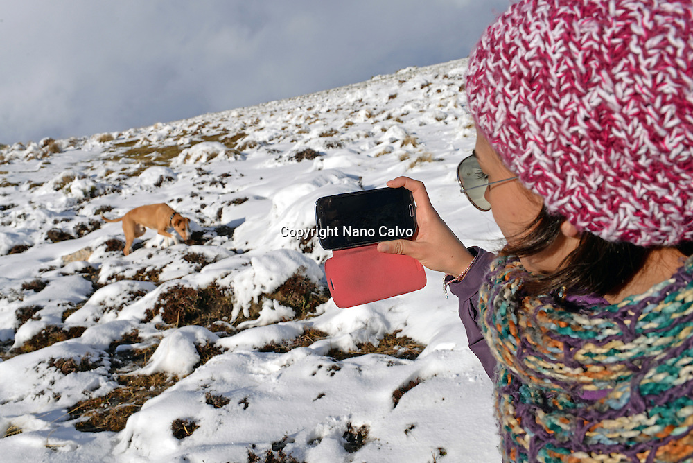 Young woman takes photos of her dog in the snow, using mobile phone