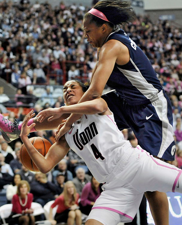 Connecticut's Bria Hartley, bottom is fouled by Georgetown's Adria Crawford, top during the second half of an NCAA college basketball game in Storrs, Conn., Saturday, Feb. 11, 2012. Connecticut won 80-38. (AP Photo/Jessica Hill)