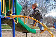 A small boy climbs up a ladder on an outdoor playscape.