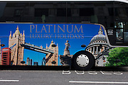 A parked tour coach for Platinum Holidays features famous London landmarks awaits passengers outside a London theatre.