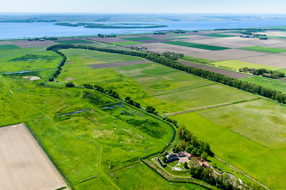 Nederland, Noordoostpolder, Schokland, 07-05-2018. Schokland, dorp en voormalig eiland in de Zuiderzee, gezien vanuit het Zuiden. Middelbuurt met hervormde kerk, onderdeel van het museum Schokland. Schokland maakt deel uit van de UNESCO Werelderfgoedlijst. Het verlagen van de grondwaterspiegel in de Noordoostpolder leidt tot inklinking waardoor het eiland steeds lager komt te liggen. Om verder wegzinken te voorkomen een hydrologische zone aangelegd. Village and former island, seen from the south. Part of the UNESCO World Heritage List. The center is the Reformed Church. Lowering the groundwater level in the Noordoostpolder leads to subsidence and causes the island the sink away. In order to prevent further decline a hydrological zone has been created. <br /> luchtfoto (toeslag op standard tarieven);<br /> aerial photo (additional fee required);<br /> copyright foto/photo Siebe Swart