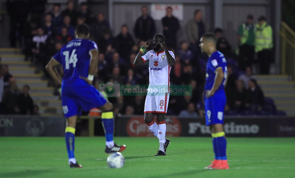 Milton Keynes Dons' Ousseynou Cisse centre asks his teammates to concentrate after they score a second goal of the game