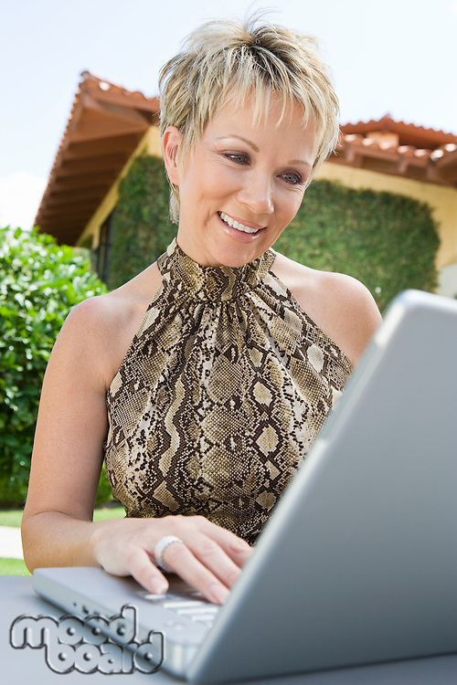 Woman using laptop in back yard