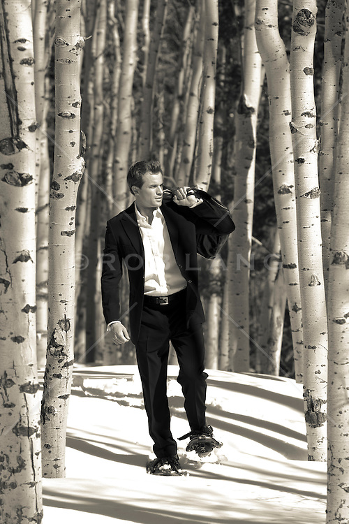 man in a suit walking through a grove of Aspen Trees in Santa Fe during the winter