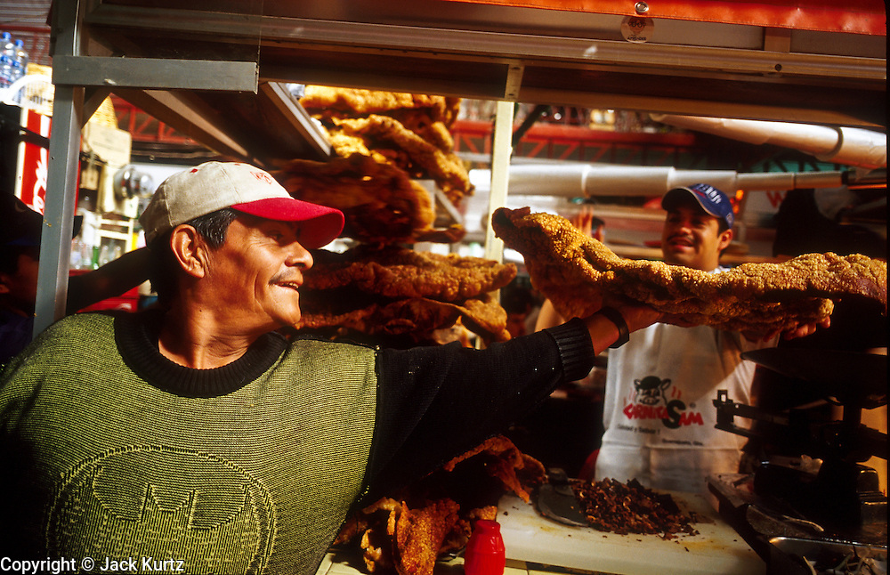 16 JANUARY 2002, GUANAJUATO, GUANAJUATO, MEXICO:  A chicharone (fried pork skins) salesman makes a delivrey to a snack bar in Mercado Hidalgo, opened in 1910, in the city of Gunajuato, state of Guanajuato, Mexico, Jan. 16, 2002. Mercado Hidalgo is the main market for Guanajuato..PHOTO BY JACK KURTZ