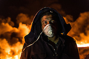 "A security guard wears a face mask to help protect his lungs from the harmful effects of the smoke. The Qayyarah oil fields and the nearby town are dotted with checkpoints guarded by Iraqi soldiers and Popular Mobilization Units. At one of the checkpoints inside the smoke-filled town, a young Iraqi soldier expressed his frustration at the involvement of foreign powers in contributing to the conflicts that have plagued his country. Speaking to an American journalist he said: ""Tell your country to take our oil. Tell them to take it all and leave us alone. We just want to live a simple life."""