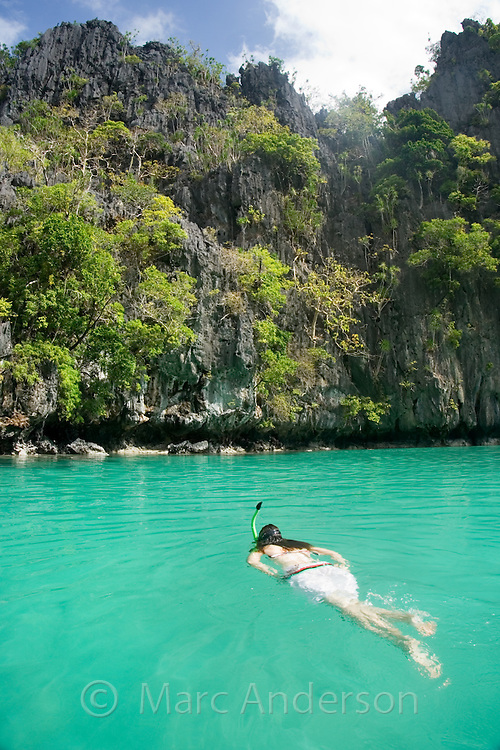 Woman snorkelling in Small Lagoon, surrounded by limestone cliffs in the Bacuit Archipelago, El Nido, Palawan, Philippines.