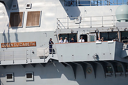© Licensed to London News Pictures. 23/06/2018. Portsmouth, UK.  Naval officers on the bridge wing aboard the Royal Navy's flagship, HMS Queen Elizabeth, as she sails into Her Majesty's Naval Base (HMNB) Portsmouth this morning, 23rd June 2018.  The aircraft carrier has been performing trials in the Northern Atlantic, including her first replenishment at sea. She is expected to remain in Portsmouth ahead of aircraft trials off the coast of the United States later this summer.Photo credit: Rob Arnold/LNP
