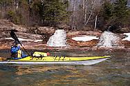 Lake Superior sea kayaker explores icy shoreline and waterfalls in spring on Michigan's Upper Peninsula.