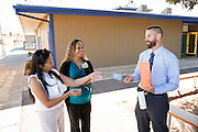 Eva Ballada, Milpitas Wal-Mart personell manager, Losa Foster, Wal-Mart assistant manager, and principal Kristian Lecours talk during a Fill-A-Bus event with school supplies donated by Wal-Mart at Randall Elementary School in Milpitas, California, on September 5, 2013. (Stan Olszewski/SOSKIphoto)