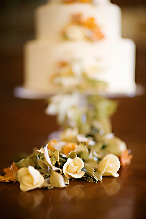 Flower arrangement laying on wooden table with a white cake in the background.