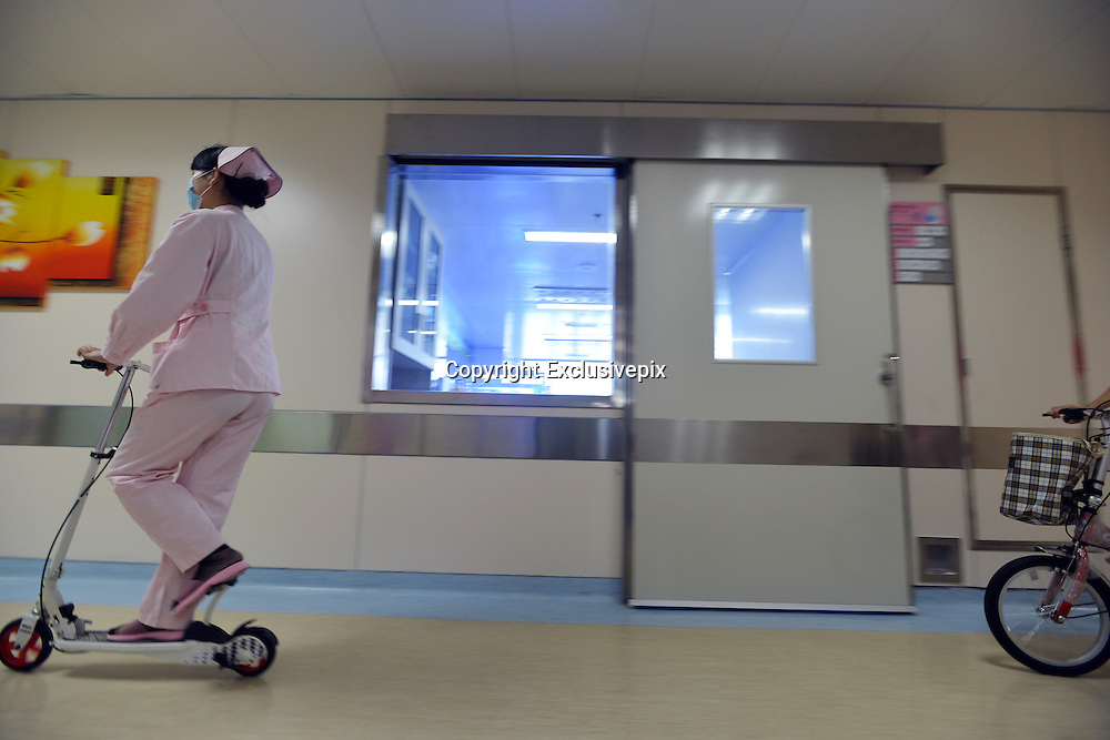 WUHAN, CHINA -  (CHINA OUT) <br /> <br /> Nurses Using Scooters To Get Around Hospital Quickly<br /> Nurses ride scooters running in the gallery of the Hubei Maternal and Child Health Hospital  in Wuhan, Hubei Province of China. Nurses using scooters to save time for faster work. <br /> &copy;Exclusivepix