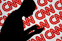 July 2, 2017 - Bydgoszcz, Poland - A man is seen holding with a smart device in front of a CNN logo in this photo illustration on 2 July, 2017. (Credit Image: © Jaap Arriens/NurPhoto via ZUMA Press)