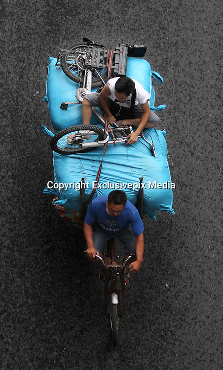 GUANGZHOU, CHINA <br /> <br /> Life On The Tricycle<br /> <br /> A porter rides a tricycle carrying cloths and people at Guangzhou International Textile City  in Guangzhou, Guangdong Province of China. More than 1,500 tricycles are active in the business district. <br /> ©Exclusivepix