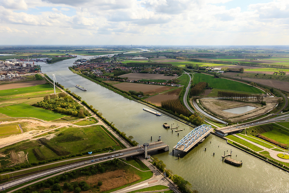 Nederland, Zeeland, Zeeuws-Vlaanderen, 09-05-2013; Sluiskil, Kanaal Gent-Terneuzen, kanaalkruising Sluiskil.  Foto richting Sluiskil.<br /> De brug in de N61 sluit zeer regelmatig voor zeeschepen en dit veroorzaakt files. Daarom zal de kanaalbrug vervangen worden door een tunnel, de Sluiskiltunnel (oplevering 2015).<br /> The pivot bridge over the canal Gent-Terneuzen (Zeeland) closes very regularly for seagoing vessels and this causes traffic jams. Therefore, the canal bridge will be replaced by a tunnel, the tunnel Sluiskil (completion 2015).<br /> luchtfoto (toeslag op standard tarieven);<br /> aerial photo (additional fee required);<br /> copyright foto/photo Siebe Swart.