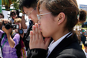 14 SEPTEMBER 2003 - CANCUN, QUINTANA ROO, MEXICO:  The daughter of Lee Kyung-hae bows at an alter for her father during a memorial service Sunday for her father, a Korean farm activist who publicly committed suicide Wednesday in Cancun to protest World Trade Organization agricultural policies, has been built where he died in a park in Cancun. Thousands of protestors opposed to the World Trade Organization and globalization have come to Cancun to protest the WTO meetings taking place in the hotel zone. Mexican police restricted most of the anti-globalization protestors to downtown Cancun, about five miles from the convention center.  PHOTO BY JACK KURTZ