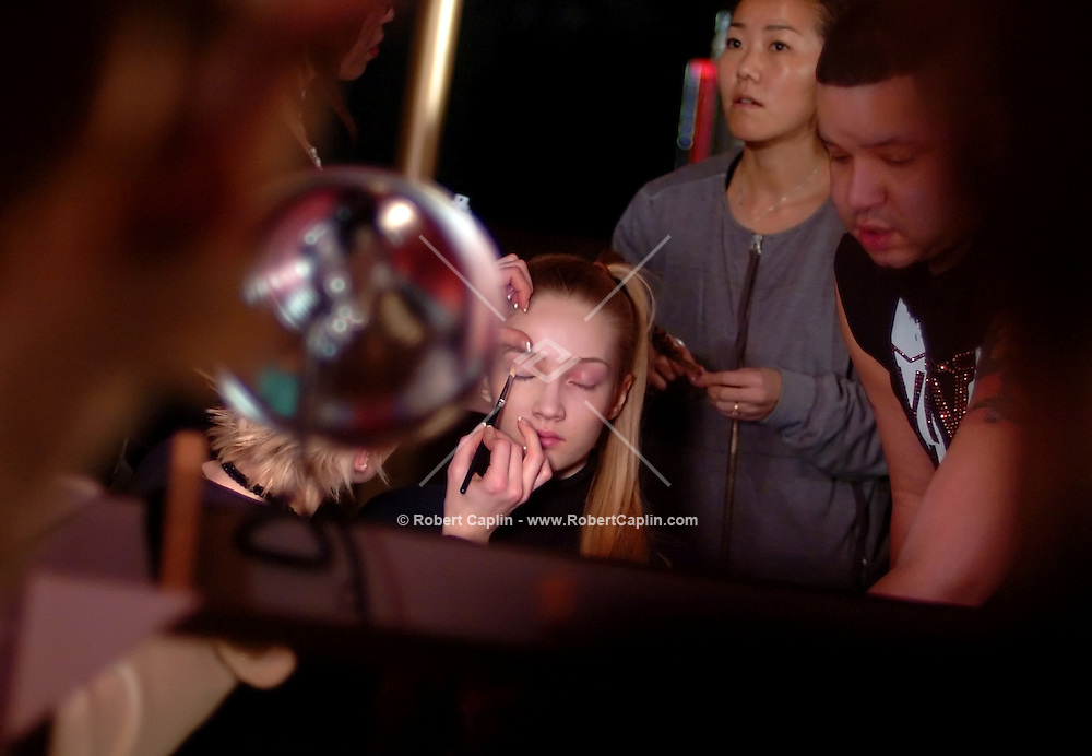 Make-up people work on a model backstage before the Malandrino Fall 2006 fashion show at Roseland Ballroom during New York Fashion Week February 10, 2006.