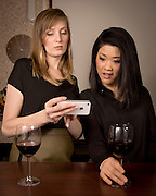 A young caucasian and a Japanese women using a smartphone together at a wine bar.