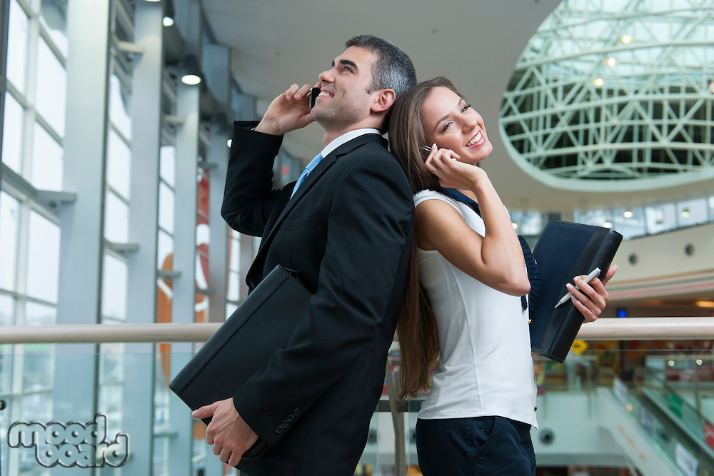 Businessman and Businesswoman back to back on mobile phones