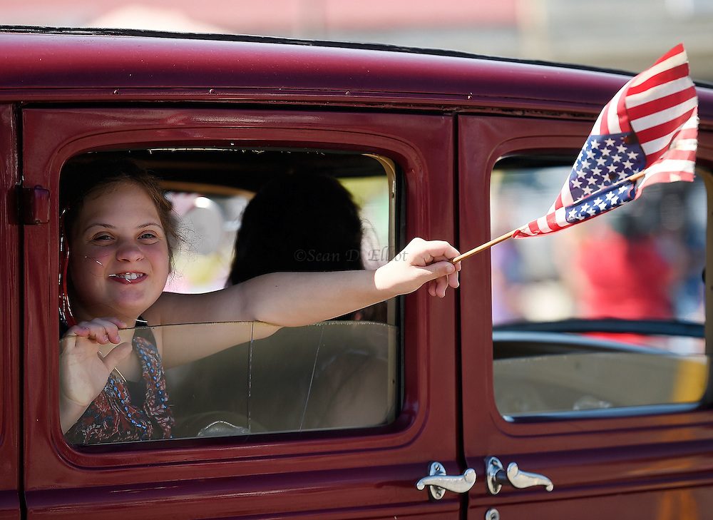 7/4/16 :: REGION :: SMITH :: Juliet Kotfel, of Noank, waves the stars and stripes from the back seat of a vintage auto in the Groton Independence Day Parade Monday, July 4, 2016. (Sean D. Elliot/The Day)