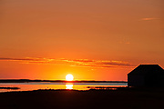 Sunrise over salt pond with boathouse silhouette, Eastham, Cape Cod, Massachusetts, USA