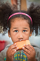 Alana, age 5, enjoys a cinnimon bun at City Market, Anchorage