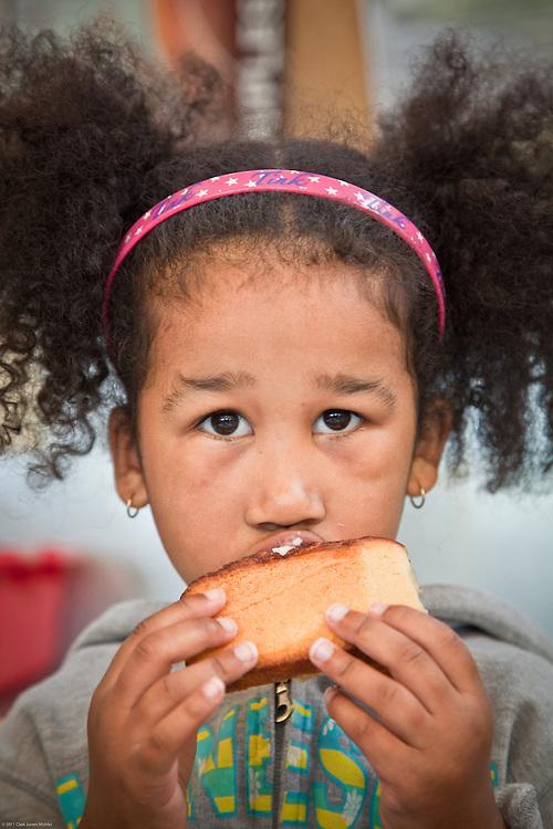 Alana, age 5, enjoys a cinnimon bun at City Market, Anchorage
