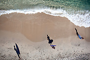 Aerial veritical view of boys with skim boards casting long shadows