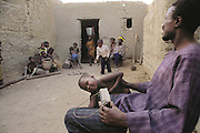 Soon after his bath, three-year-old Mamadou earns a reprimand as he climbs over his father, Soumana Natomo, who is trying to listen to a soccer game on the family radio. In the village of Kouakourou, Mali, on the banks of the Niger River. Published in Material World, page 19. The Natomo family lives in two mud brick houses in the village of Kouakourou, Mali, on the banks of the Niger River.
