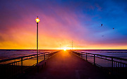 The sun rising directly over the end of the New Brighton Pier, Christchurch