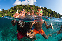 The Children of Tola Bali, Shot in Indonesia<br /> <br /> When our dive boat arrived at the village of Tola Bali, on the Indonesian island of Pura (near Alor), we were greeted by dozens of the village's children, canoeing and swimming out to pose for photographs, and get a handout of something sweet.  Most have homemade goggles, no fins, or even bathing suits.  But that doesn't slow them down at all.  The smiles, laughs, and frolicking were highly contagious, with many of the divers jumping into the water to play along with the kids.<br /> <br /> Unfortunately, there are no model releases available for this image